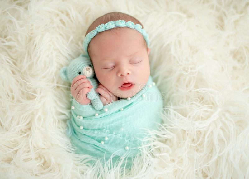 Sleeping newborn in blue headband. Sleeping adorable newborn baby child, in blue colored blanket and with floral headband royalty free stock photography