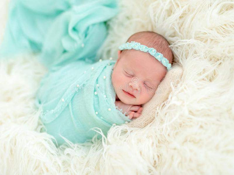 Sleeping newborn in blue headband. Sleeping adorable newborn baby child, in blue colored blanket and with floral headband stock photography