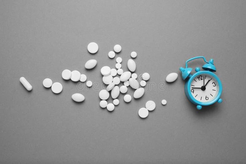 Sleeping pills and an alarm clock, insomnia concept. Stress and sleep problems stock photos