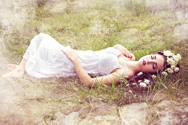 Sleeping pretty woman with flower in hair. Bride with natural flowers in hair lying on grass stock photo