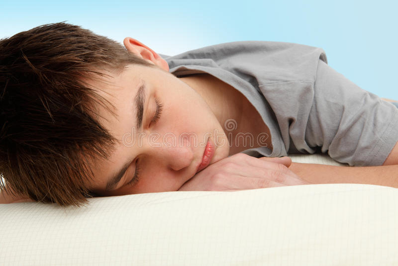 Sleeping teenager. Closeup of a teen boy sleeping on a bed stock images