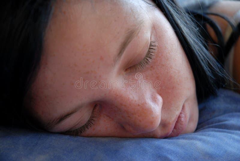 Sleeping teenager. Beautiful teenager sleeping on a blue sofa stock photo
