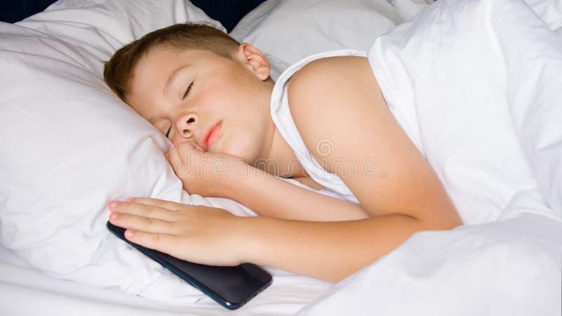 Sleeping teenager boy holding his smartphone. gadget addiction. Sleeping teenager boy holding his smartphone stock photos