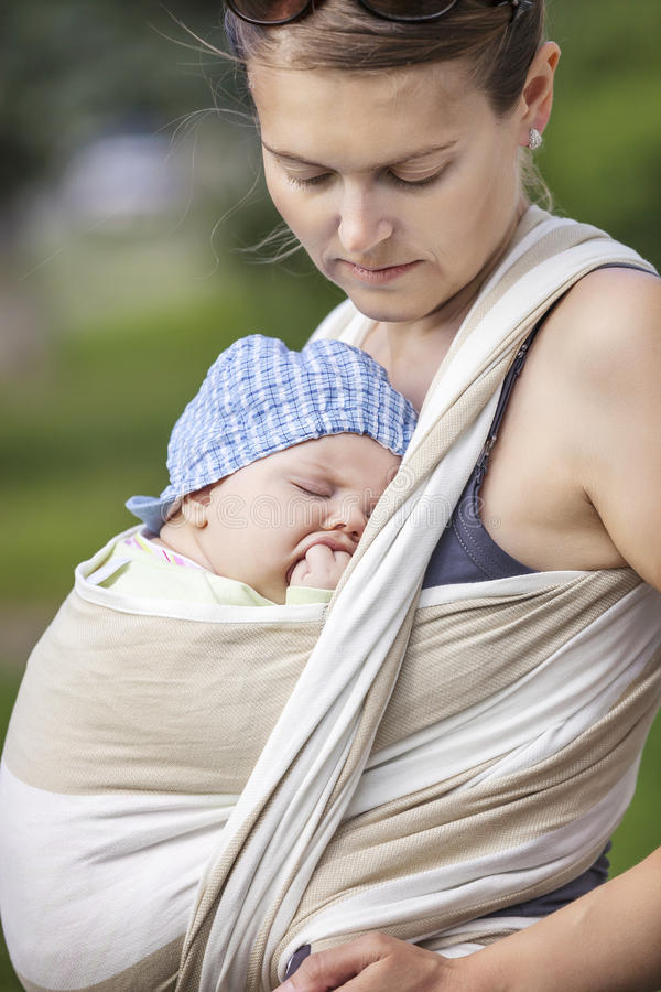 Sleeping toddler boy in sling, mother carrying son. Outdoors stock image