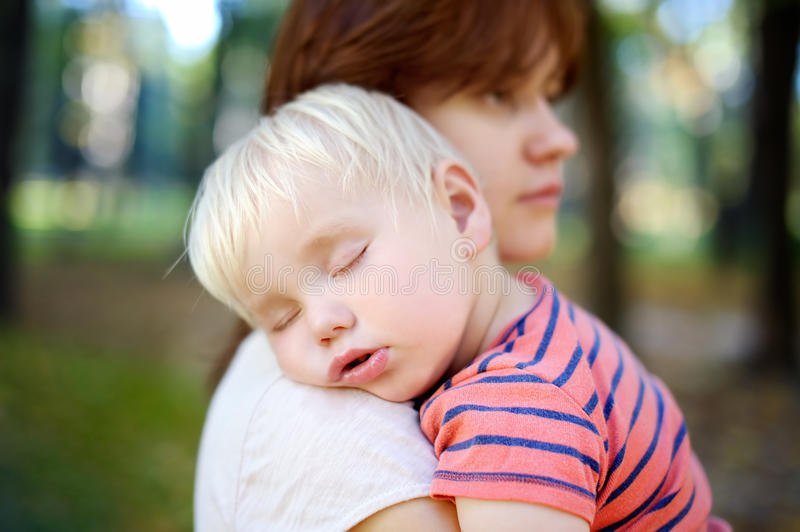 Sleeping toddler boy. Young mother holding her sleeping toddler son stock images