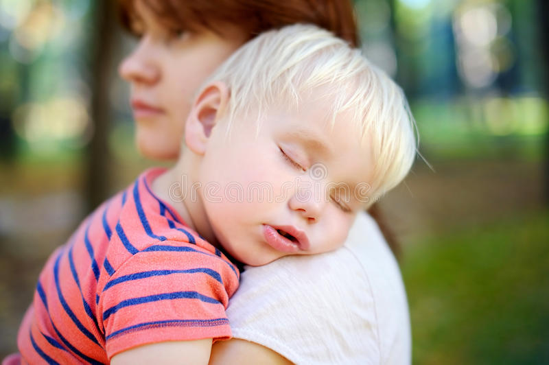 Sleeping toddler boy. Young mother holding her sleeping toddler son royalty free stock photography