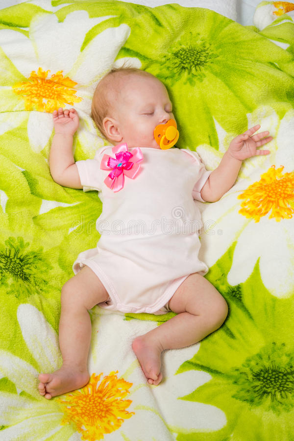 Sleeping two month baby in the crib. A two-month baby girl Europeans lies on a soft bed on colored coverlet stock photo