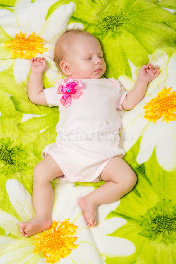 Sleeping two month baby in the crib. A two-month baby girl Europeans lies on a soft bed on colored coverlet stock photography