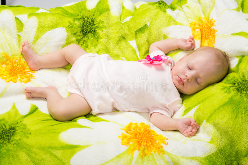 Sleeping two-month girl. A two-month baby girl Europeans lies on a soft bed on colored coverlet royalty free stock images