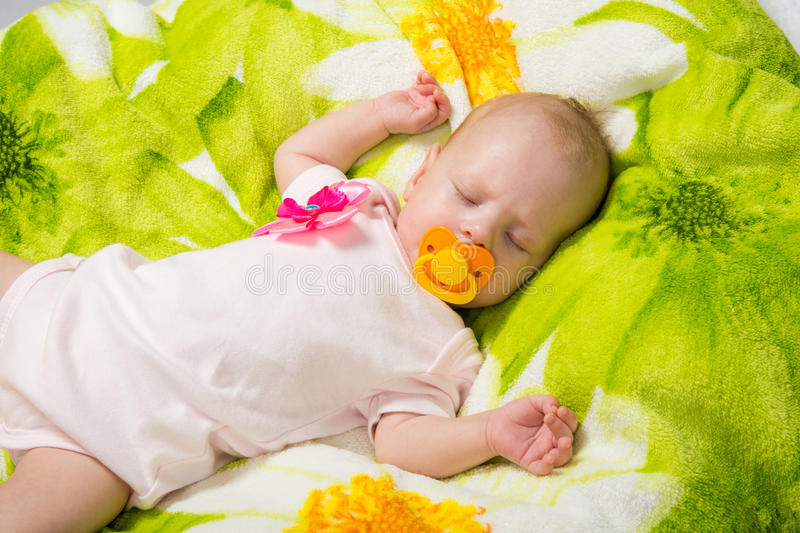 Sleeping two-month girl sucking a pacifier. A two-month baby girl Europeans lies on a soft bed on colored coverlet stock photo