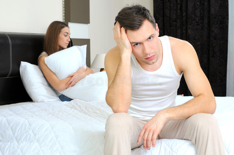 Sleeping. Upset men having problem sitting on the bed with his girlfriend royalty free stock photos