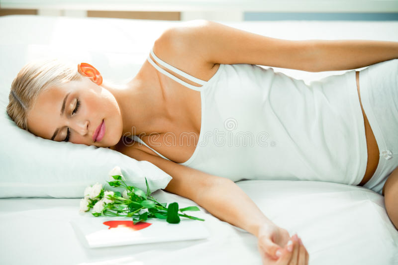 Sleeping woman. On bed with valentines card and flowers royalty free stock photos