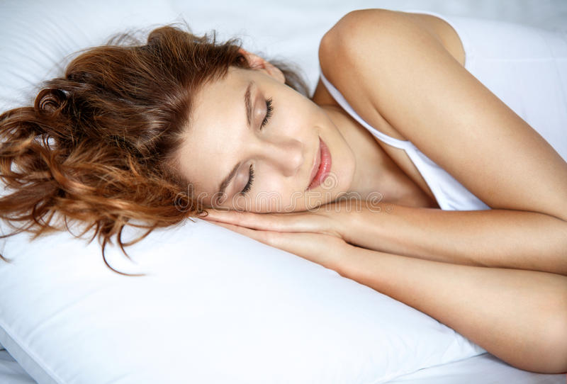 Sleeping woman in bed. Beautiful brunette woman lying on a pillow royalty free stock images