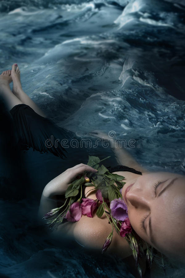 Sleeping woman in a dark water of a river stock photo