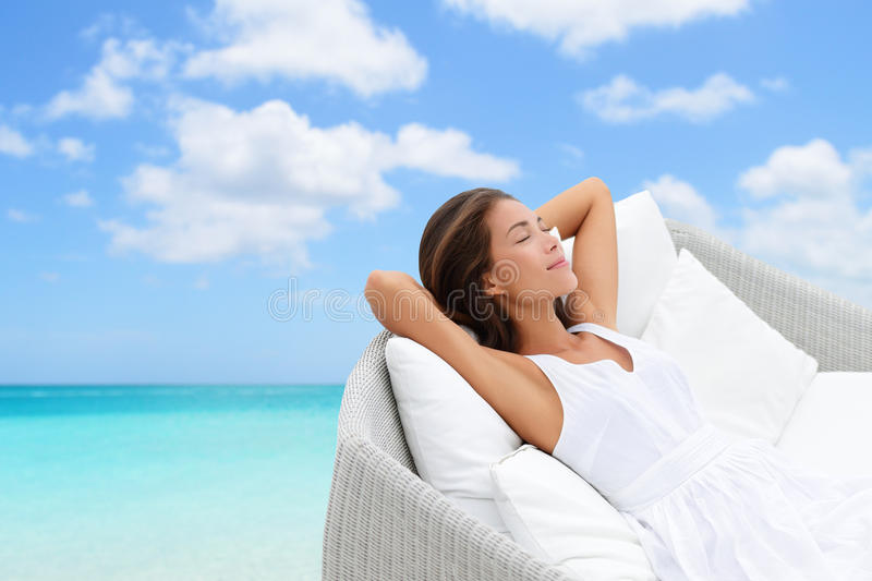 Sleeping woman relaxing lounging on a outdoor sofa. Sleeping woman relaxing lounging on white outdoor sofa day bed lounger on beach ocean background. Asian girl royalty free stock image