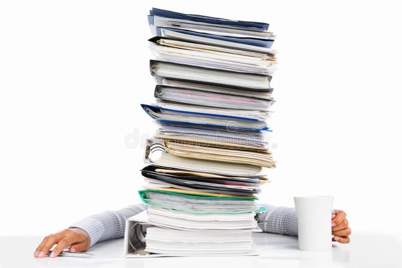 Sleeping worker behing high pile of paperwork stock photo