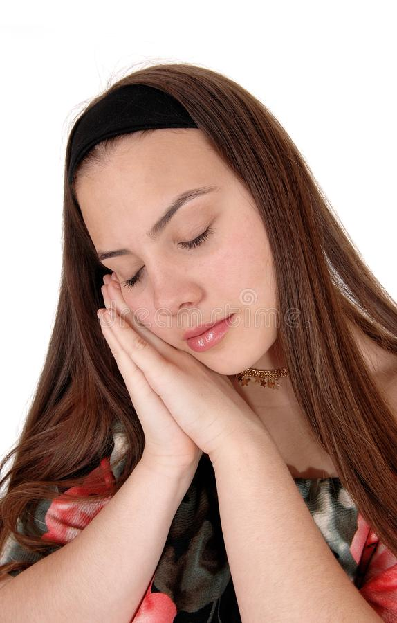 Sleeping young teenager on her hands. A beautiful teenager girl holding both hands on her face and sleeping.with her long brunette hair, isolated for white stock images