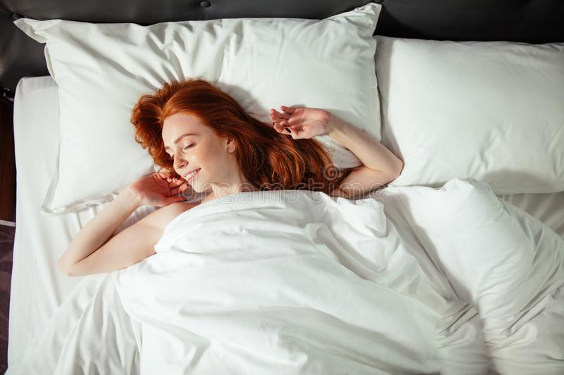 Sleeping young woman lies in bed with eyes closed. top view stock images