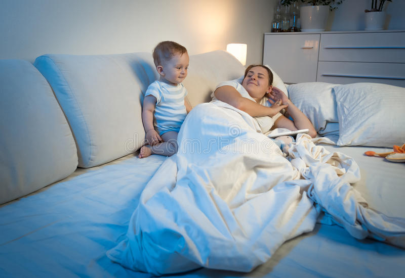 Sleepless baby waking up mother sleeping in bed. Sleepless baby boy waking up mother sleeping in bed stock photos