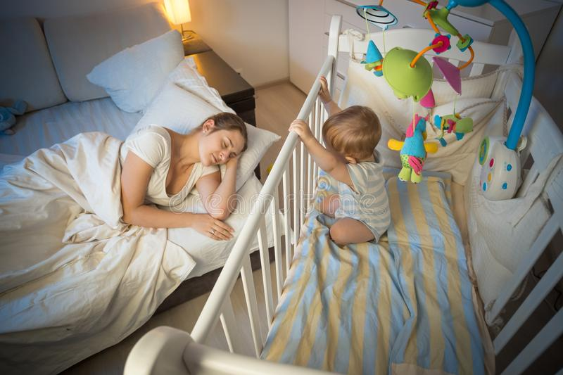 Sleepless 9 months old baby boy looking at tired mother sleeping in bed. Sleepless 9 months old baby looking at tired mother sleeping in bed royalty free stock images