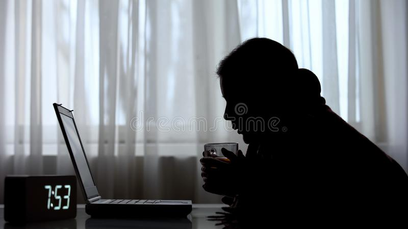 Sleepless woman drinking tea working on laptop in morning, job responsibilities stock image