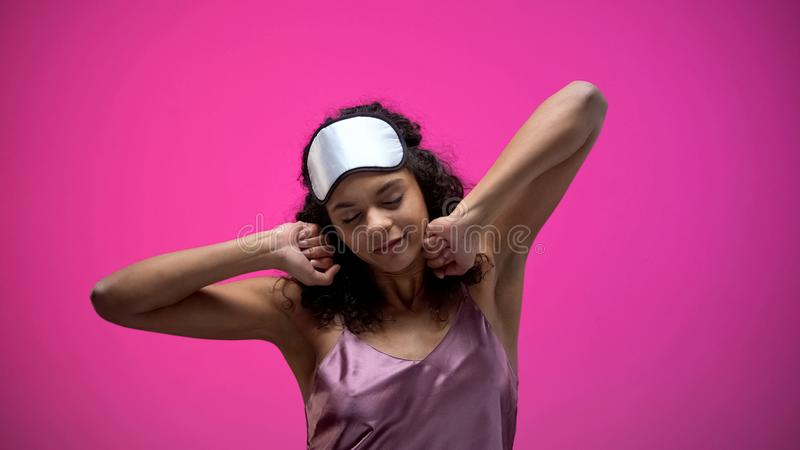 Sleepy African-American woman stretching after waking up in morning, energy. Stock photo stock images