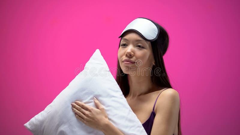 Sleepy asian female in pajamas and eye mask holding pillow, preparing for sleep stock image