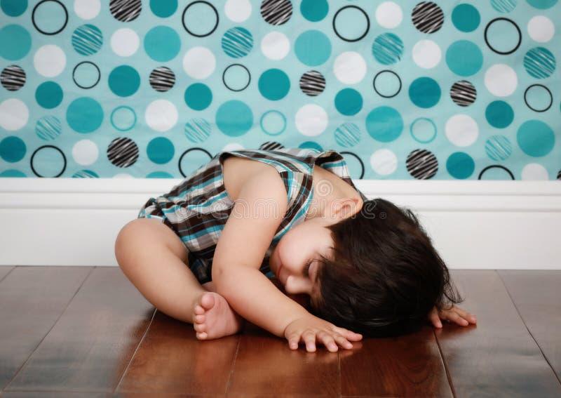 Sleepy baby. A cute baby boy laying on the studio floor stock photo