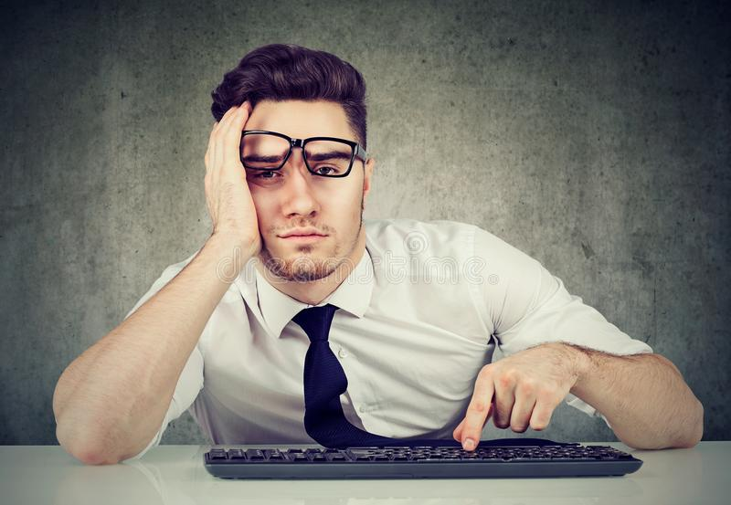 Bored man employee sitting at desk has no motivation to work. Sleepy bored man employee sitting at desk has no motivation to work stock image