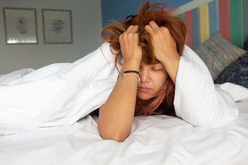 Sleepy drowsy young woman suffering hangover headache with eyes closed in bed at home.Insomnia woman migraine headache in royalty free stock photography