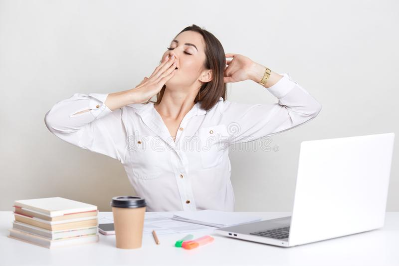 Sleepy European woman yawns and stretches, keeps hand on mouth, wears white shirt, uses laptop computer, books, isolated over whit stock photo