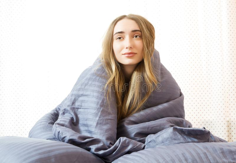 Sleepy girl in the morning in bed, Young beautiful woman sleeping wrapped in a blanket. Sleepy beauty woman resting on bedroom royalty free stock photography