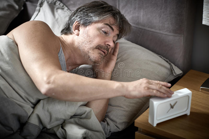 Sleepy man in bed wake up. Sleepy man in bed wake up with alarm clock stock image