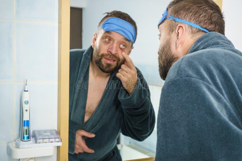 Sleepy man looking at mirror stock photo