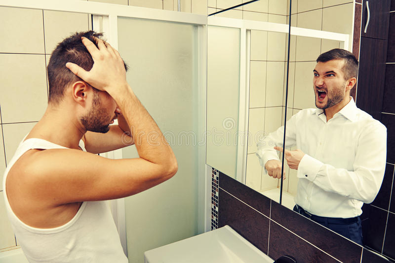 Sleepy man looking in the mirror. At his angry reflection stock image