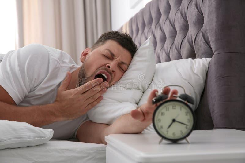 Sleepy man turning off alarm clock at home royalty free stock images