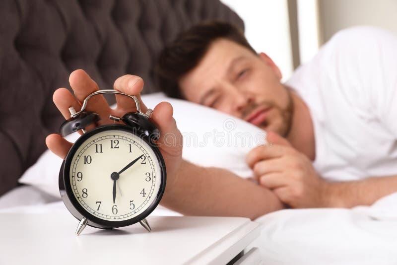 Sleepy man turning off alarm clock on nightstand royalty free stock images
