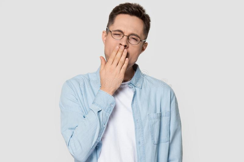 Man yawning covering mouth with hand standing on grey background. Sleepy man wearing glasses and jean shirt standing on grey white background studio shot, guy royalty free stock images