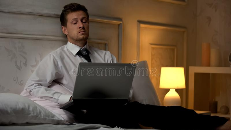 Sleepy manager working computer in bedroom late at night, start up. Stock photo stock photography