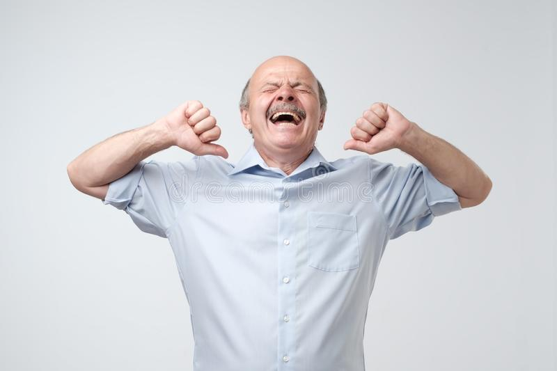 Sleepy mature bald man with mustache is yawning, because he is tired. stock photo