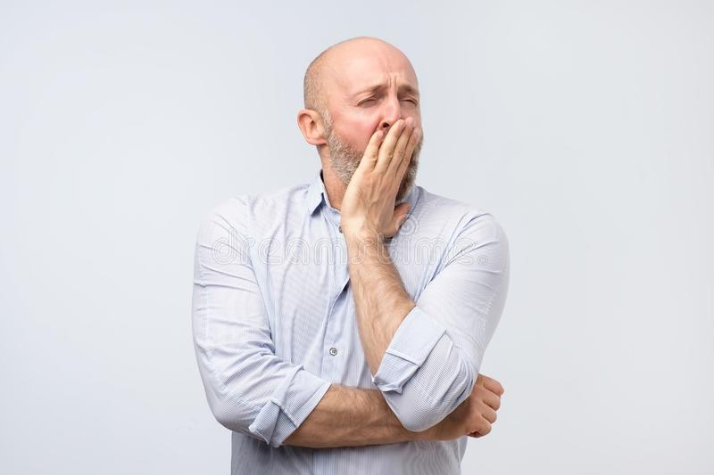 Sleepy mature man yawning after hard working day, closing his mouth with hand stock photography