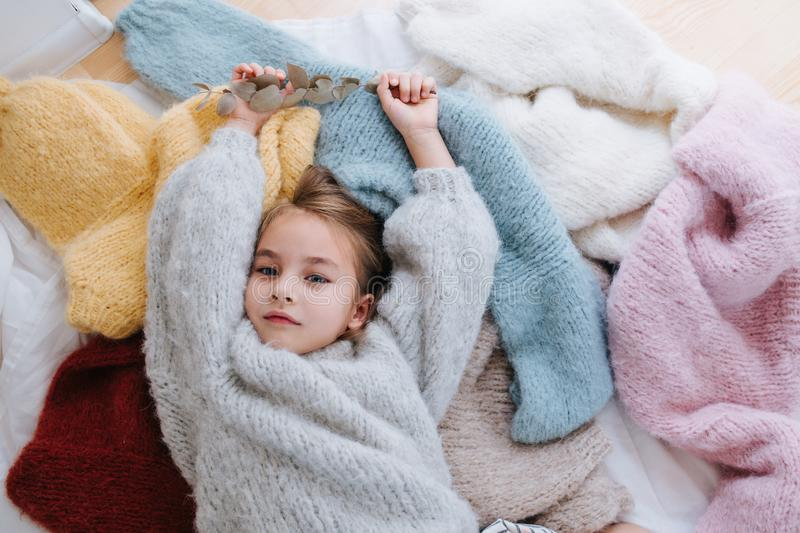 Sleepy little girl is lying on a pile of soft multi-colored sweaters on the floor stock photo