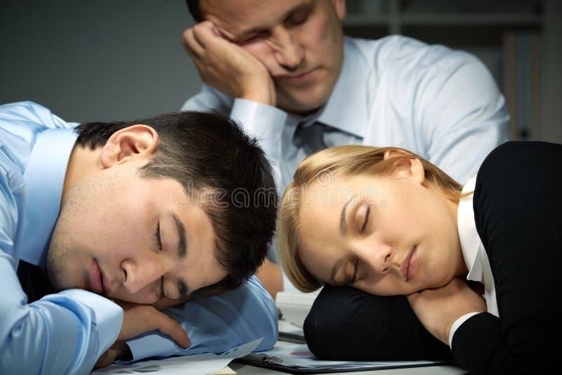 Sleepy team. Three business people falling asleep at work stock images