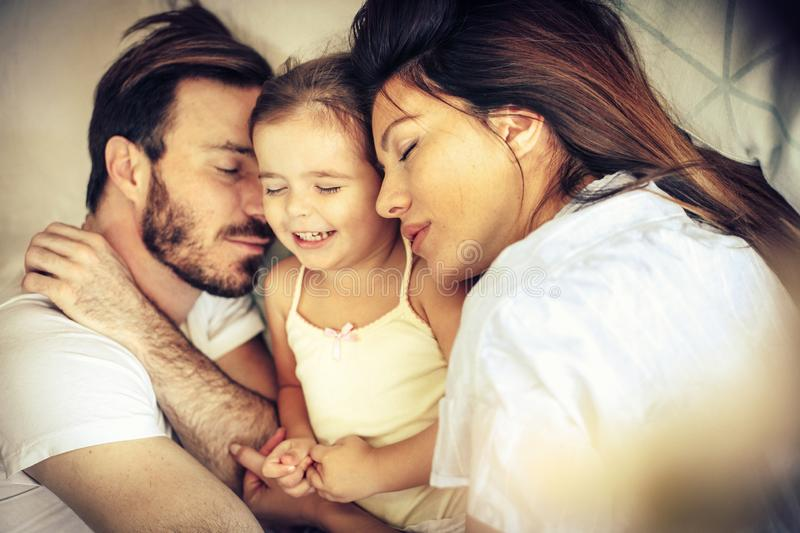 Sleepy time. Young family sleeping together in bed stock image