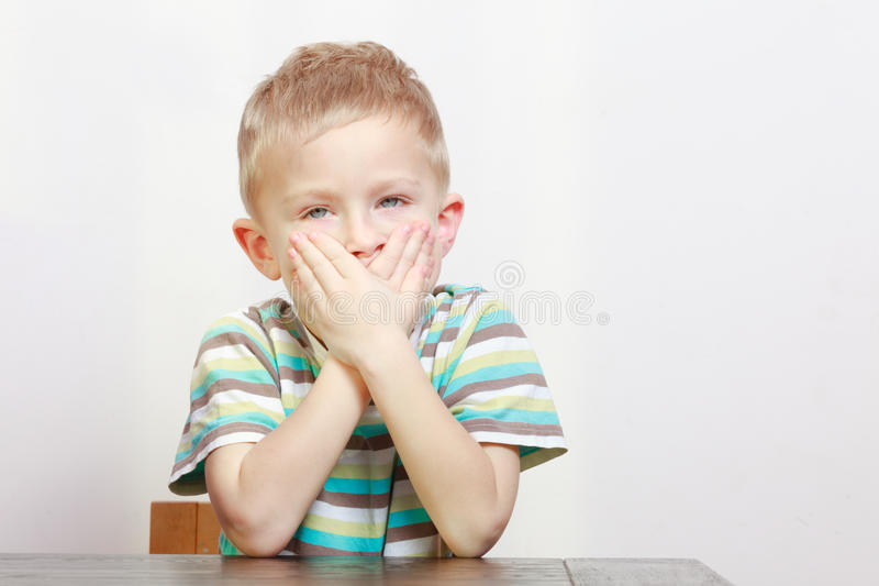 Sleepy tired boy child kid yawning covering mouth. At home. royalty free stock image