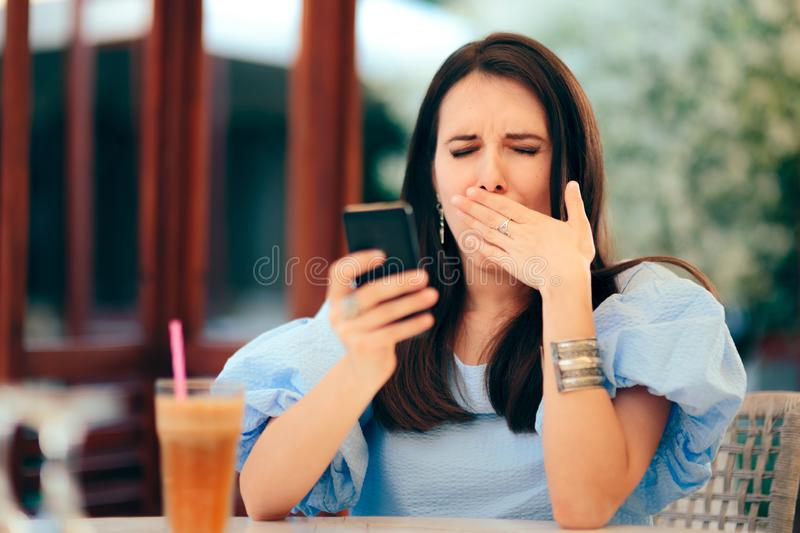 Sleepy Woman Being Bored with Her Smartphone in a Restaurant. Girl yawning watching boring things on the internet to pass the time royalty free stock photos