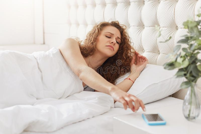 Sleepy woman with curly hair turns off alarm on smart phone, wakes early up in morning, tries to get up, doesn`t want to go for w. Ork, feels comfortable at bed stock photography