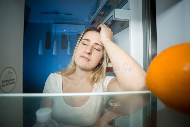 Sleepy woman leaning on refrigerator shelf and trying to sleep. Portrait of sleepy woman leaning on refrigerator shelf and trying to sleep royalty free stock image