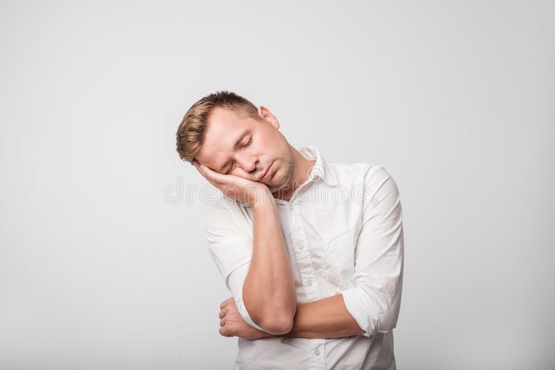 Sleepy young caucasian man in white shirt yawning, closing his mouth with hand, isolated on gray background. royalty free stock images