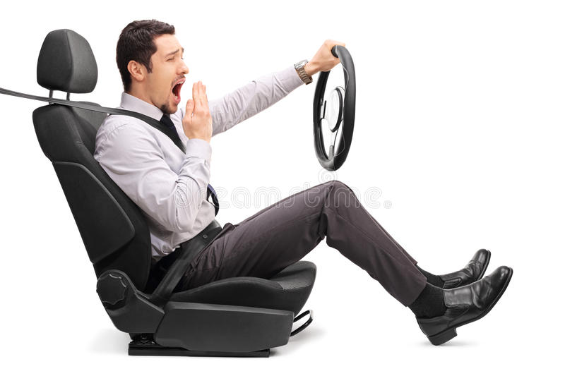 Sleepy young guy holding a steering wheel. Profile shot of a sleepy young guy holding a steering wheel seated on a car seat on white background royalty free stock photo
